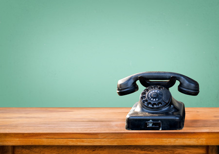 Retro black telephone on wood table with vintage green eye light wall background