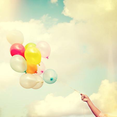 Mano de la muchacha que sostiene los globos multicolores hace con un efecto retro filtro de Instagram de la vendimia, el concepto de día de nacimiento feliz en el verano y la fiesta de luna de miel de la boda (el tono del color de la vendimia) Foto de archivo
