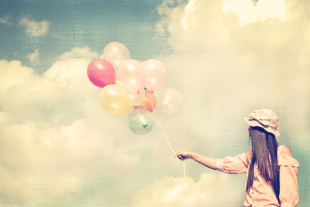 moods: Vintage photo of  Happy young red hair woman  holding colorful balloons and flying on clouds sky background.