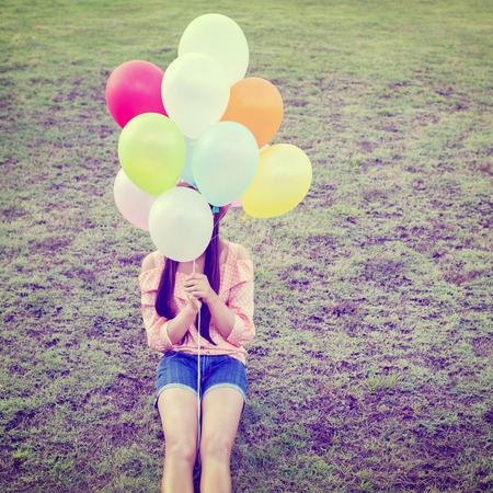 spaciousness: Vintage photo of  Happy young girl holding colorful balloons and sitting on grass field, instagram filter
