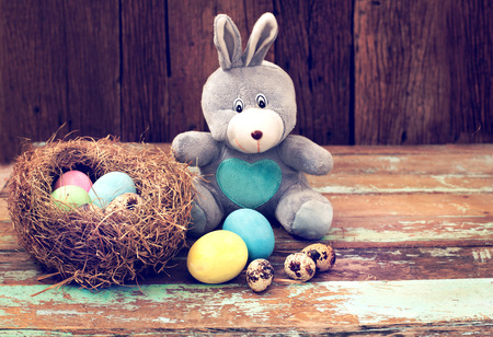 basket: Vintage Easter eggs colorful with bunny doll on wood table, instagram filter