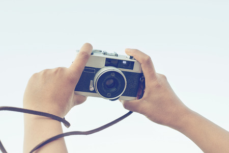 season photos: woman hand holding camera for selfie, vintage effect