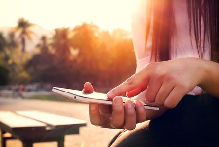 Close up von einer Frau mit mobilen Smartphone im Sonnenuntergang mit outdoor, Natur Hintergrund. (Vintage-Farbton) Standard-Bild - 39648388
