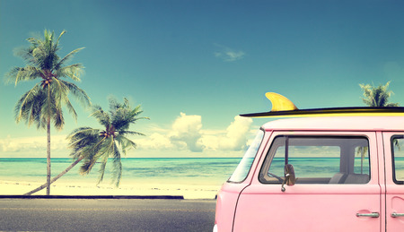 sunny beach: Vintage car in the beach with a surfboard on the roof Stock Photo