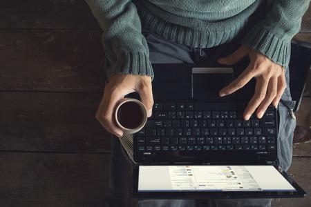 teclado: Top vista masculinos manos usando la computadora port�til y la taza de caf� en las manos sentado en un piso de madera