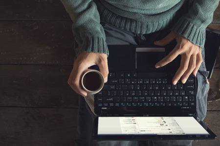 Uppifrån manliga händerna med bärbar dator och kaffekopp i händerna sitter på ett trägolv