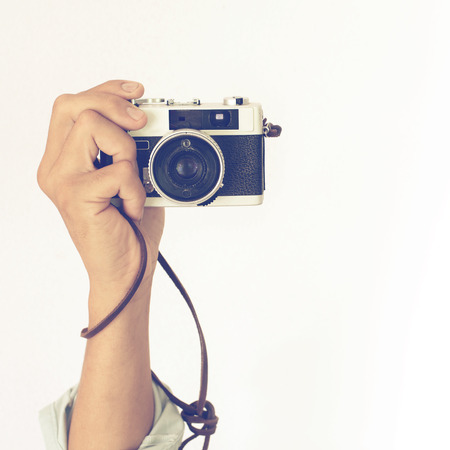 photographing: Mans hands holding vintage old camera with retro  Stock Photo