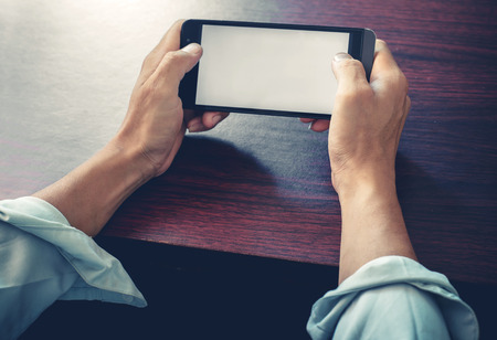 mobile business: Close up of a business man using mobile smart phone   at wooden table with retro
