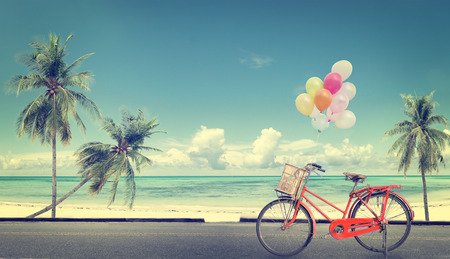 vintage bicycle with balloon on beach blue sky concept of love in summer and wedding honeymoon