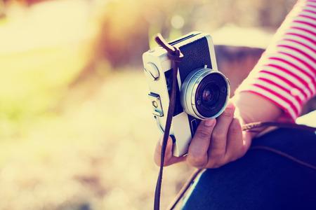 Joven fotógrafo de la muchacha de la vendimia inconformista mano que sostiene la cámara retra