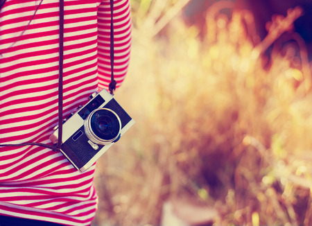 female photographer: Vintage young hipster girl photographer with retro camera in holiday travel Stock Photo