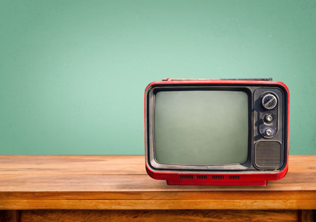television screen: Retro red television on wood table with vintage aquamarine wall background