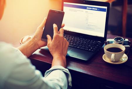 the working day: Vista lateral de tiro de hombre de negocios joven que trabaja en su computadora portátil y el uso de teléfono inteligente sentado en la mesa de madera en una cafetería con efecto retro filtro Foto de archivo