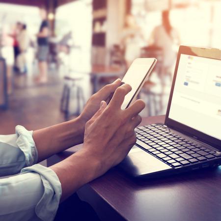 젊은 비즈니스 남자의 측면보기 샷 자신의 노트북에서 작동 레트로 필터 효과와 커피 숍에서 나무 테이블에 앉아 스마트 폰을 사용하여 스톡 콘텐츠