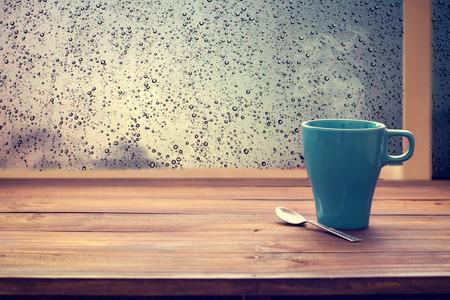 Heiße Kaffeetasse auf Holztisch mit Regentropfen Fenster (Jahrgang Farbton)