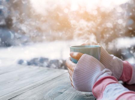 copa: Vista lateral de la mano femenina que sostiene la taza de café caliente en el invierno