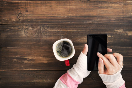 Above view of female hand holding smart phone with hot cup of coffee on wood table Archivio Fotografico