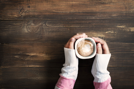 capuchinos: Por encima de vista de la mano femenina que sostiene la taza de café caliente en la mesa de madera Foto de archivo