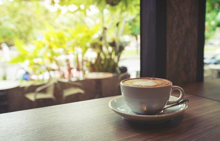 Kopp kaffe på bord i café Morgonljus, vintage eller retrofärgad tonad