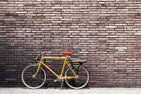 bicycles: Retro bicycle on roadside with vintage brick wall background