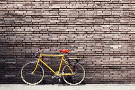 Retro cykel på vägarna med vintage tegelvägg bakgrund