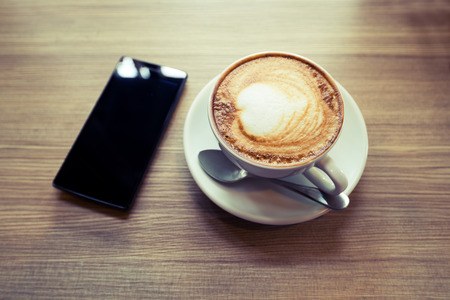 Above view of smart phone with hot cup of coffee on wood table. Photo in vintage color image style.