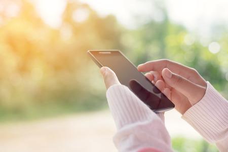 Žena pomocí mobilního chytrý telefon outdoor, příroda pozadí