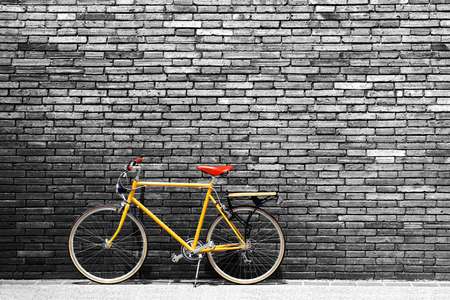 yellow house: Vintage bicycle on roadside with black and white brick wall background Stock Photo