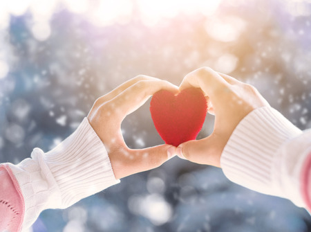 heart hands: Female hand holding red heart up to the sun during morning with a snow in winter , love and valentine concept