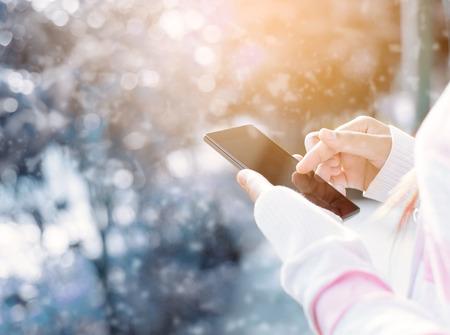 Mujer que usa el móvil teléfono inteligente al aire libre, la naturaleza de fondo Foto de archivo