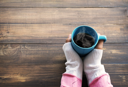 Above view of female hand holding hot cup of coffee on wood table. Photo in vintage color image style.