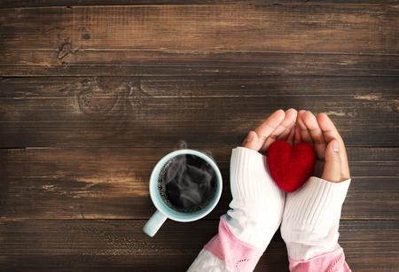 Above view of female hand holding red heart with hot cup of coffee on wood table. Photo in vintage color image style.