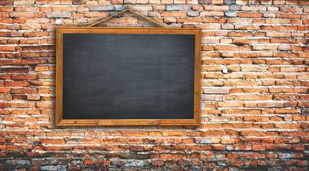 繩子上黑色的黑板。磚牆的紋理使用您的附加信息 版權商用圖片