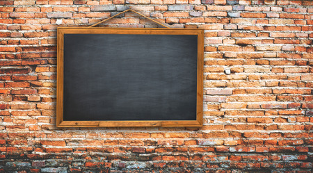 Black chalkboard on a rope. brick wall texture use for your add message