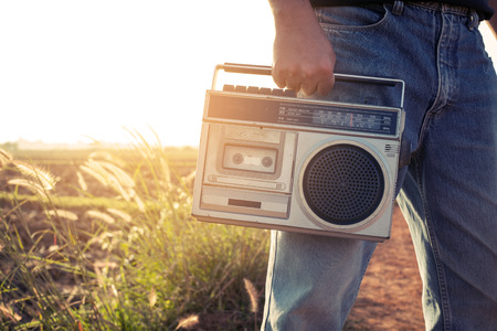 Radio: Man hand holding vintage radio on nature background