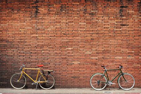 ビンテージのレンガ壁背景を活用した沿道のレトロな自転車 写真素材
