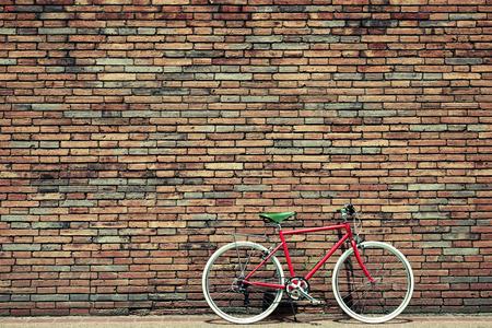 bicicleta retro: Bicicleta retro en el borde de la carretera con el fondo de la pared de ladrillo de la vendimia
