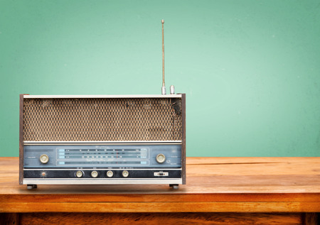 vintage photo: Old retro radio on table with vintage green eye light background