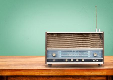 escuchar: Antigua radio retro en la mesa con la vendimia fondo claro ojo verde