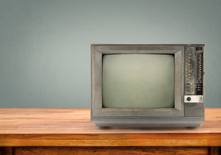 television show: Retro television on wood table with vintage  wall background Stock Photo