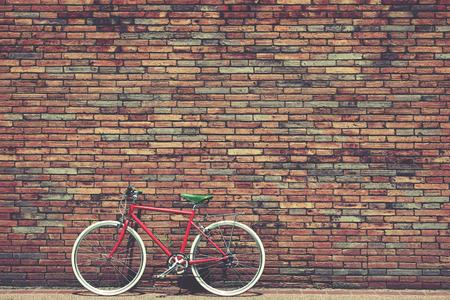 Bicicleta retro en el borde de la carretera con el fondo de la pared de ladrillo de la vendimia