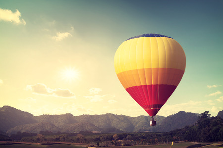 Hot air balloon over mountain, vintage retro filter effect