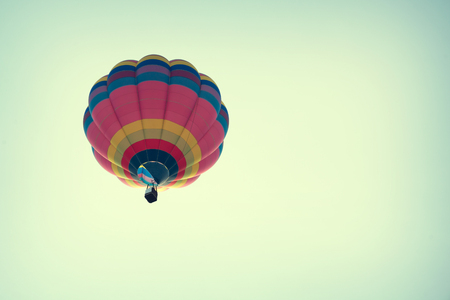 hot air balloons festival: Multicolor hot air balloon on blue sky, vintage retro filter effect