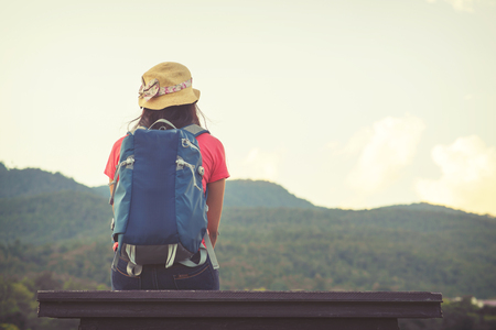 Travelers Asian woman with backpacks and sit looking landscape of the mountainous. vintage color effect
