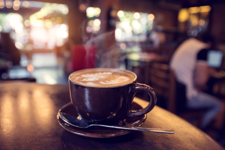 Cup of coffee on table in cafe with people in dark coffee shop - shallow depth of field