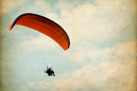 risk free: paramotor over sky with clouds, vintage paper art texture - retro style Stock Photo