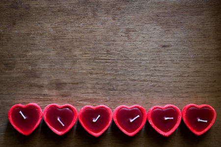 marco madera: Red candle heart shape lined on blank wooden background - love symbol. vintage color tone Foto de archivo