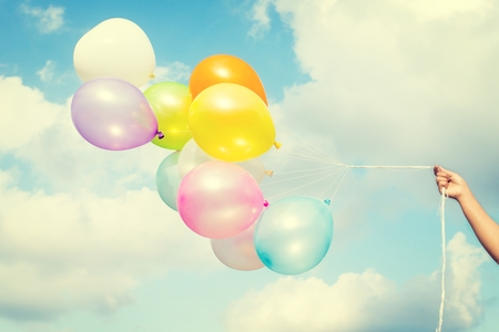 birthday balloon: Woman hand holding colorful balloons on blue sky concept of birthday in summer and wedding honeymoon - vintage color effect