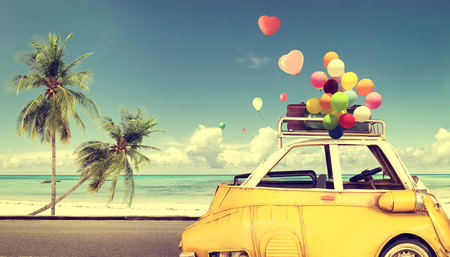 復古黃色車在沙灘上藍天心臟五顏六色的氣球 - 夏季婚禮的愛情觀。蜜月之旅 版權商用圖片