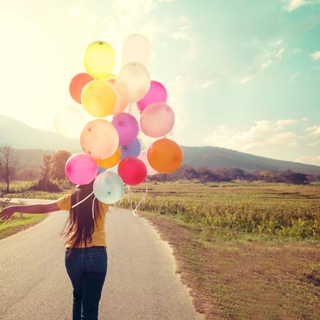 Glück Teenager-Mädchen mit bunten Luftballons genießen in den frühen Morgenstunden auf Grünland. Alles Gute zum Geburtstag Partei. Vintage-Farbton-Effekt